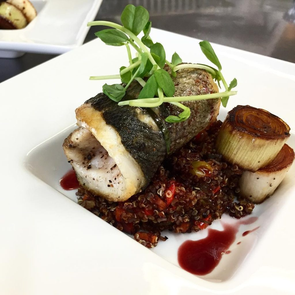 Roasted Branzino -European Sea Bass, preserved lemon quinoa, braised leeks and hibiscus sauce. by Presidential Gourmet