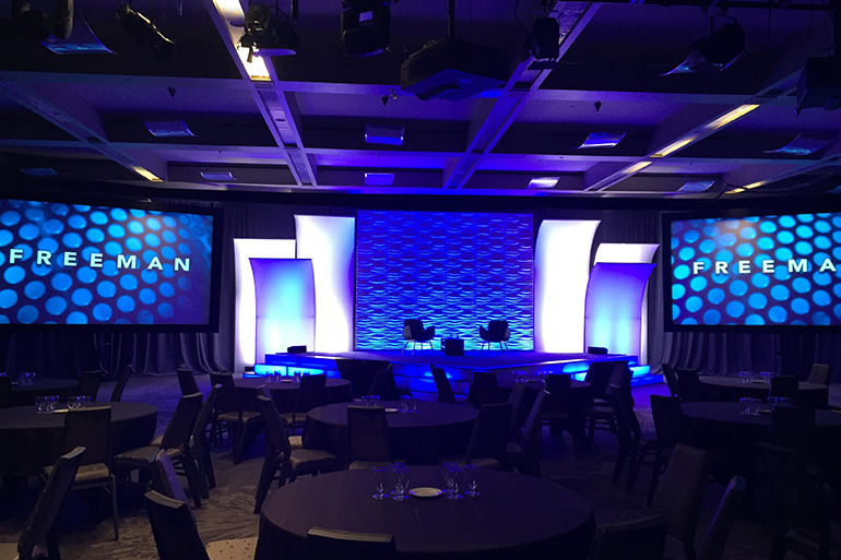 Gobos, lighting to colour spandex pieces & wave wall to create textured powerful backdrop to reflect company brand Freeman audio visual
