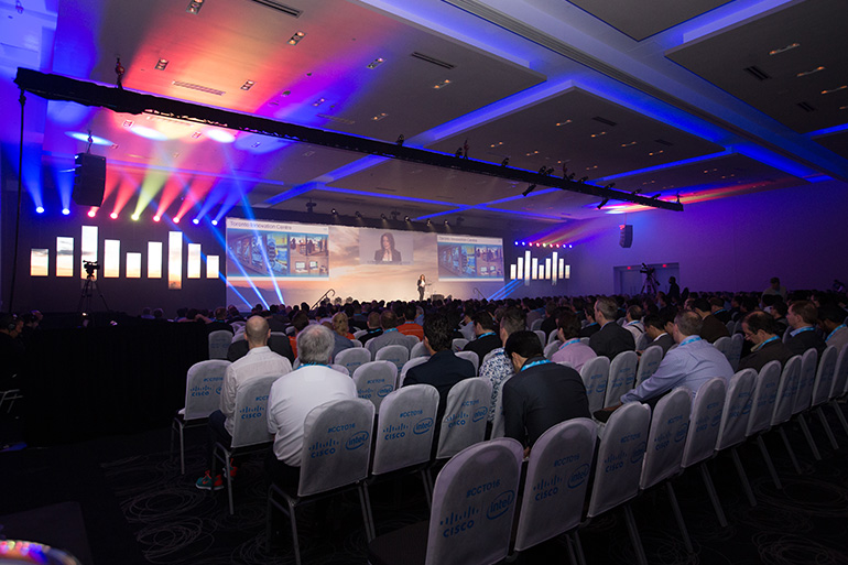 bb Blanc for the 2016 Cisco Connect Toronto production. 70' wide screen with a 3 projector blend. LED video panels shaped as the Cisco Bridge to display digital content. LED moving lights above each panel and on stage to complete the set. Photo: Skylite Images